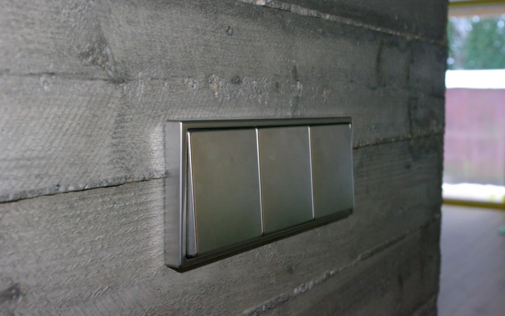 Jung LS 990 nerūdijančio plieno mygtukai ant betoninės sienos